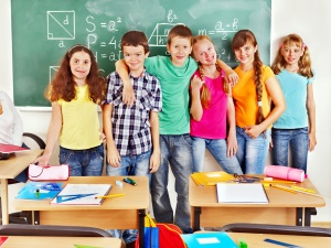 Group of school children in the classroom - http://blog.selectmytutor.co.uk/wp-content/uploads/2014/07/happy-little-math-students-uk.jpg